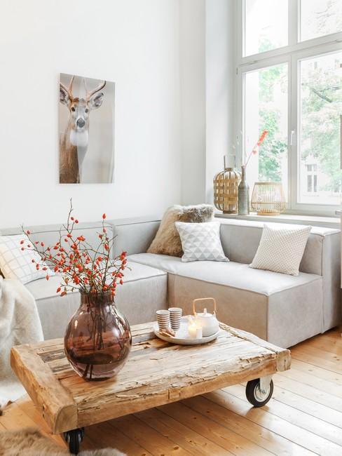 Jasny salon z narożną sofą, drewnianym stolikiem kawowym oraz rustykalnymi dekoracjami