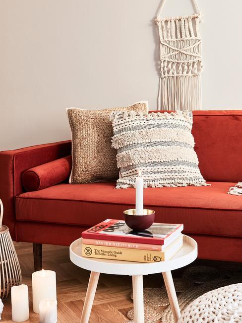 Wypoczynkowa część domowego biura z czerwoną kanapą, białym stolikiem oraz dekoracjami
