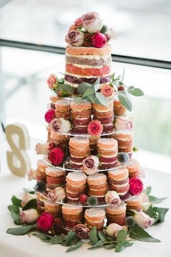 Tort weselny wykonany z babeczek w stylu naked cake wraz z kwiatami jako dekoracja