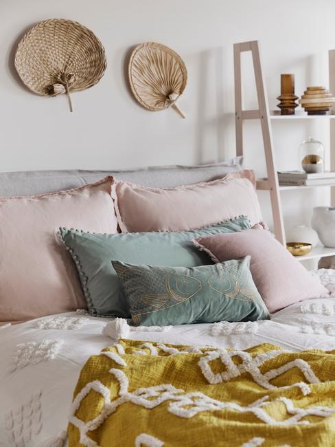 Zaścielone łóżko z poduszkami w kolorze pudrowego różu i miętowej zieleni
