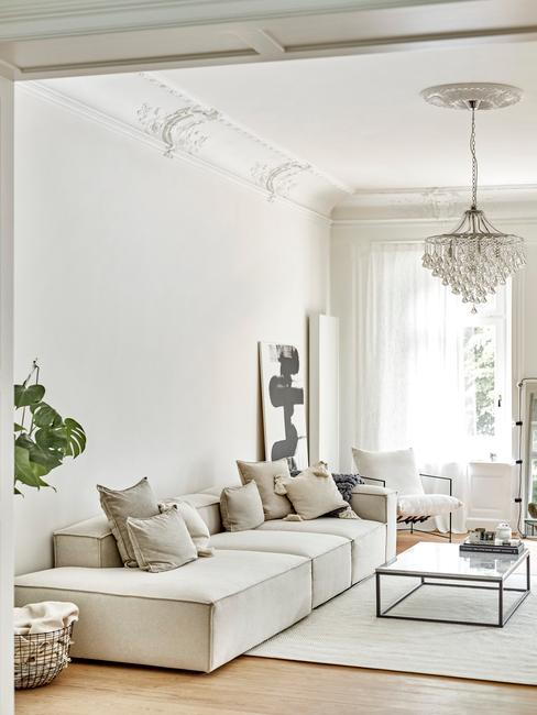 Biały salon z dużą sofą, szklanym stolikiem kawowym oraz roślinami