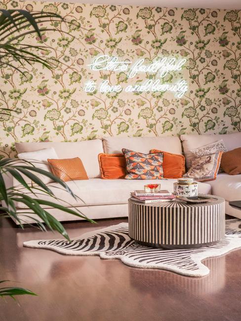 Salon z wzorzystą tapetą na ścianie, dużą, narożną sofą, okrągłym stolikiem kawowym oraz dywanem z zebrę
