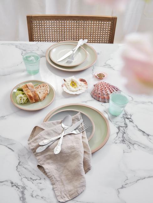 Elegancka aranżacja stołu wykonanego z marmuru oraz kamionkowej zastawy