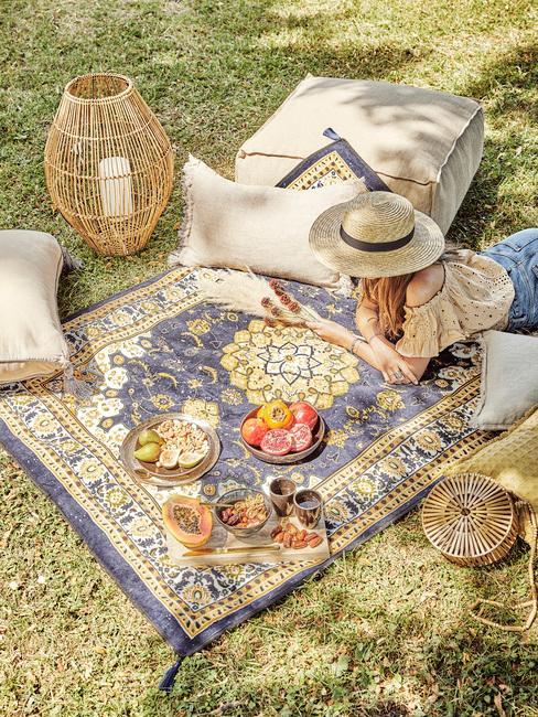 Niebieski dywan ze wzorami lniane poduszki oraz drewniana latarenka w stylu boho