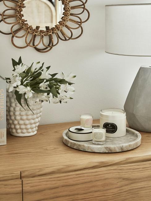 Zbliżenie na drewnianą komodę z ceramicznym wazonem oraz marmurową tacą