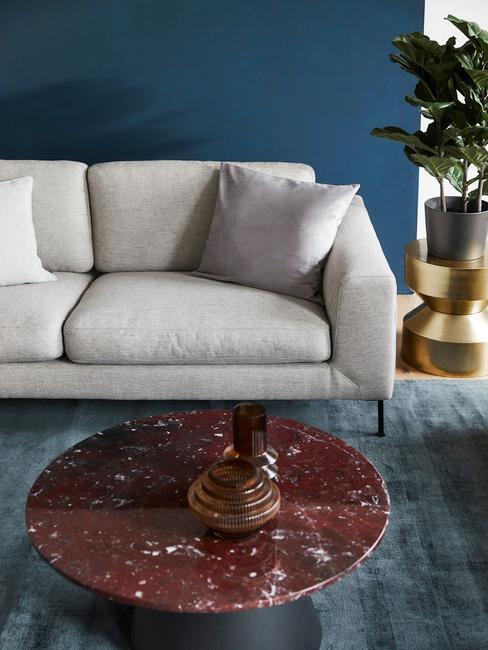Jasnoszara sofa z marmurowym stolikiem w kolorze czerwonym w niebieskim salonie