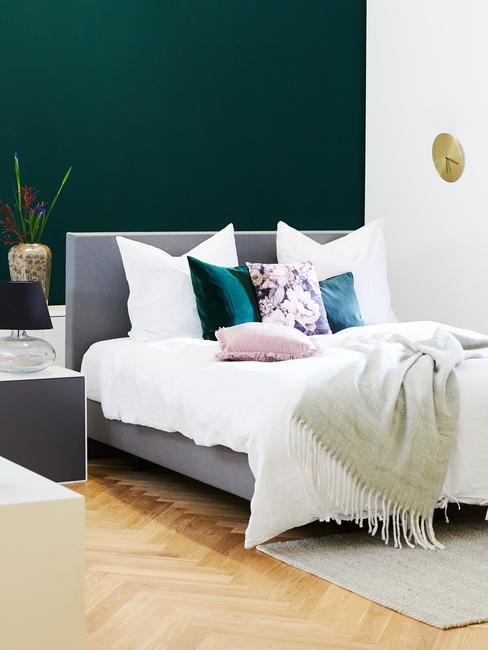 Sypialnia w stylu skandynawskim z łożkiem, białą pościelą i jedną ścianą w ciemnozielonym kolorze