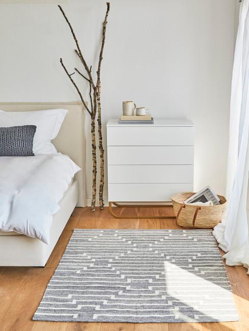 Minimalistyczna sypialnia w stylu scandi z białą komodą, dywanem oraz galęziami obok łóżka