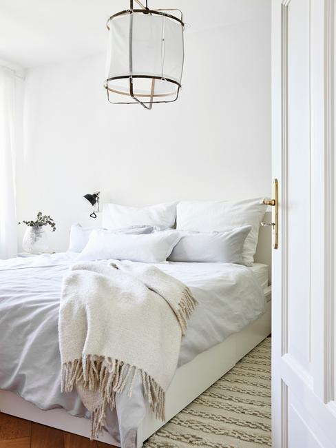 Sypialnia w bieli, złotą wiszącą lampą oraz roślinami