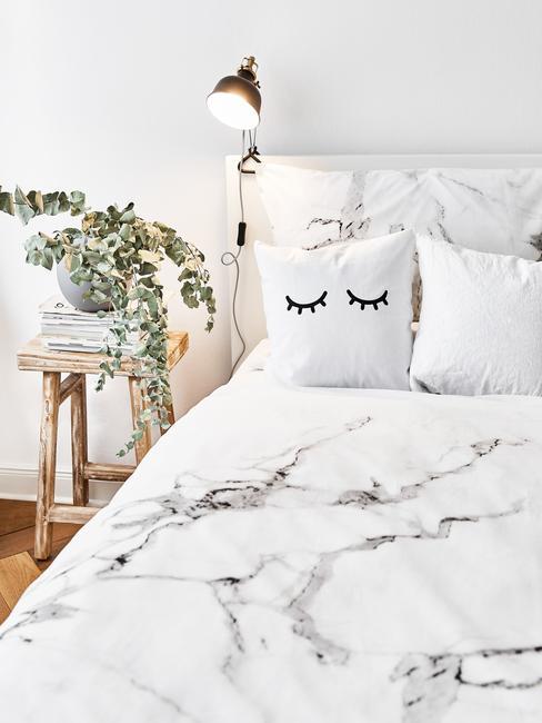 Zbliżenie na łóżko z pościelą ze wzorem sylizowany na marmur oraz roślinę w donicznce