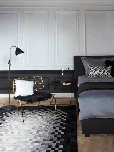 Biało - czarny pokój z łożkiem, stoliiem nocnym, krzesłem w złotej ramie oraz czarno-białym dywanem