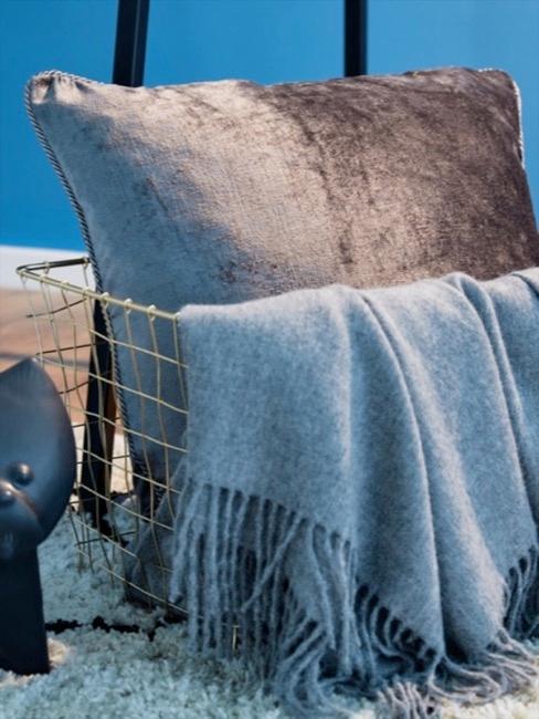 Plaid en laine baby alpaga dans un panier en métal avec coussin gris foncé devant le mur bleu.