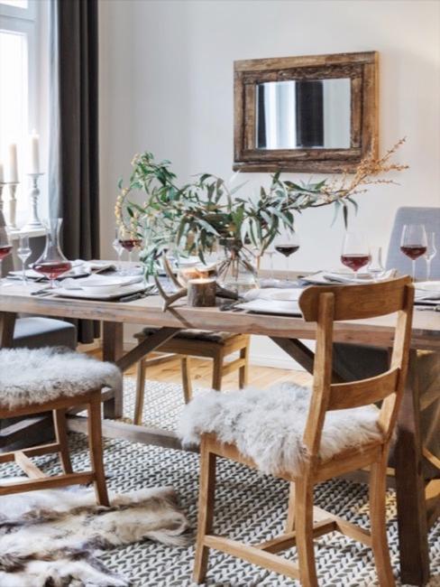 Eetkamer in cottage stijl met houten tafel en stoelen en schapenvacht
