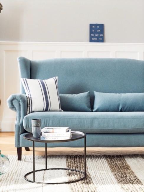 Blauwe zitbank met gestreept kussen, gestreept vloerkleed en een kleine metalen salontafel