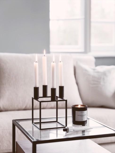 Dettaglio di salotto in design purista, divano chiaro, tavolino trasparente e candelabro minimal