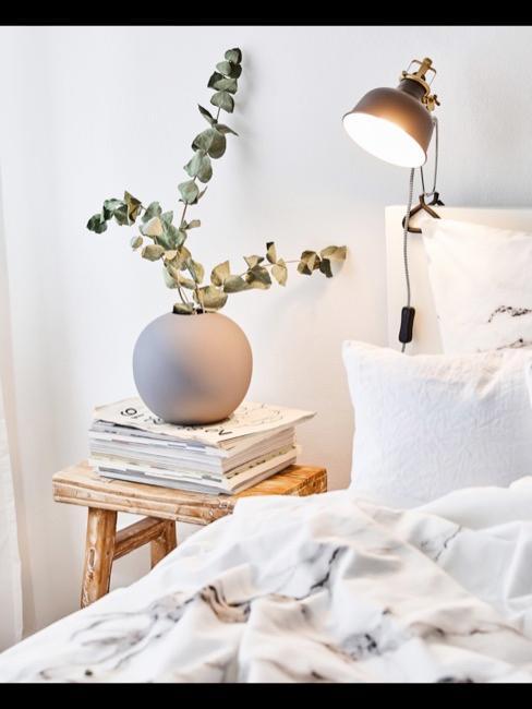 Dettaglio letto bianco con luce e comodino con vaso