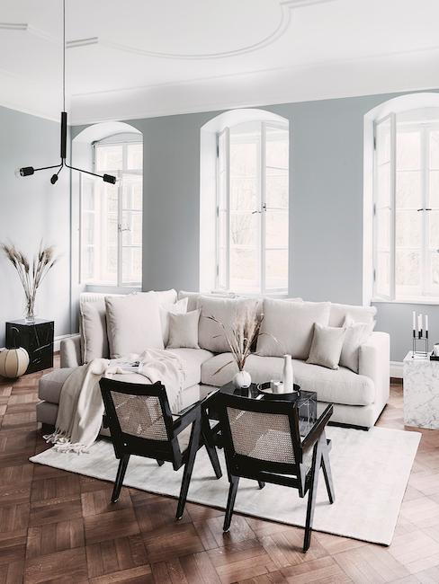Jasna sofa w salonie, dywan i stolik kawowy oraz krzesła z plecionki wideńskiej