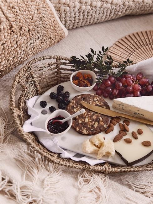 Assiette de fromages en gros plan avec raisins, amandes et pain