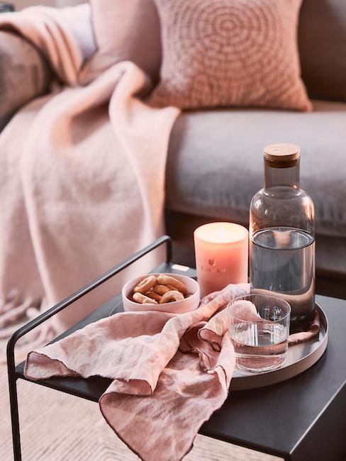 Table basse avec serviette de table en lin rose pastel sur plateau décoratif devant le canapé avec coussins et plaid rose pastel