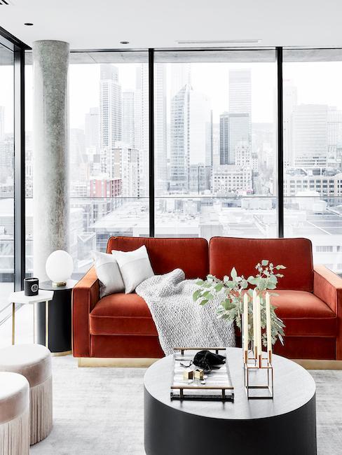 salón moderno con ventanas grandes, una mesa de centro redonda y un sofá de color rojo óxido