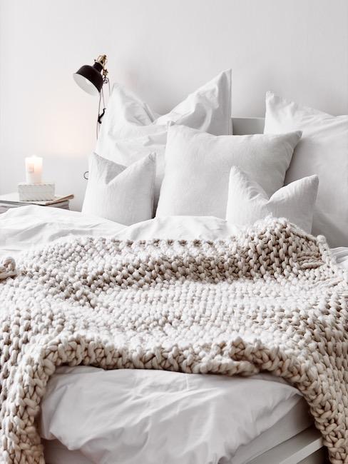 Cama blanca con cubrecamas de lana color crema y lámpara de pared
