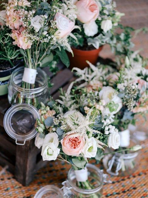Kleine boeketten bloemen in glazen potjes