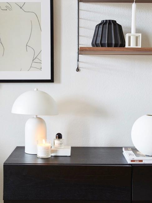 Biała lampa w otoczeniu dekoracji na ciemnym drewnianym kredensie