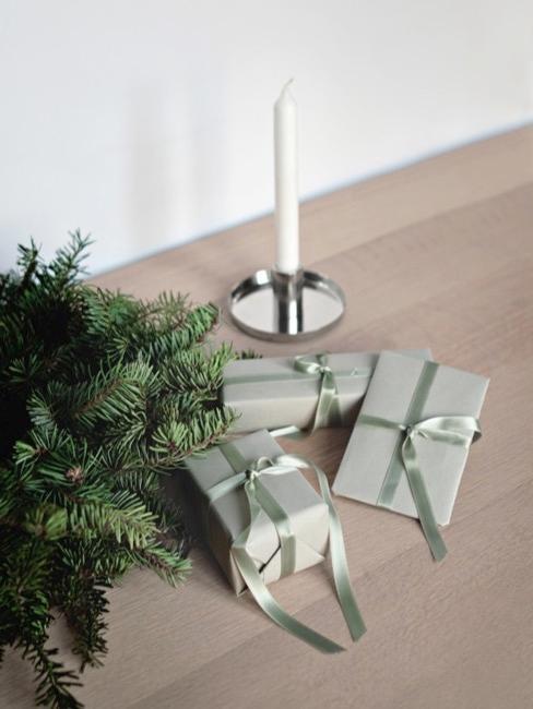 Prezenty opakowane w zielony papier umieszczone na półce w otoczeniu świecy i gałązki jodły