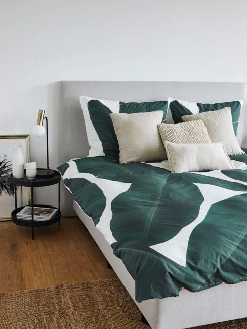Camera da letto con copriletto in stile tropicale con foglie e cuscini bianchi