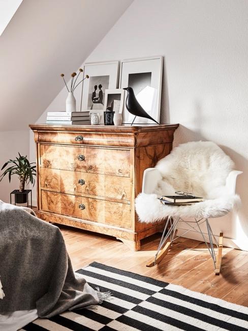 Antyczna komoda w jasnym pokoju, obok krzesło bujane