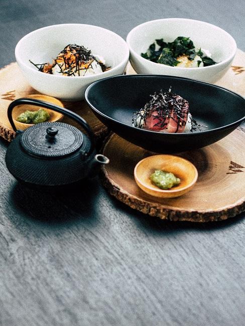 Mehrere Bowl-Schüsseln mit Essen und einer Teekanne auf Holzplatten auf dem Esstisch