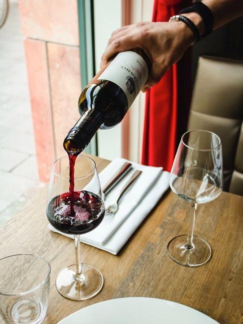 Rode wijnglazen op houten tafel met wijnglazen en wijnfles met rode zijn en rode gordijnen op de achtergrond