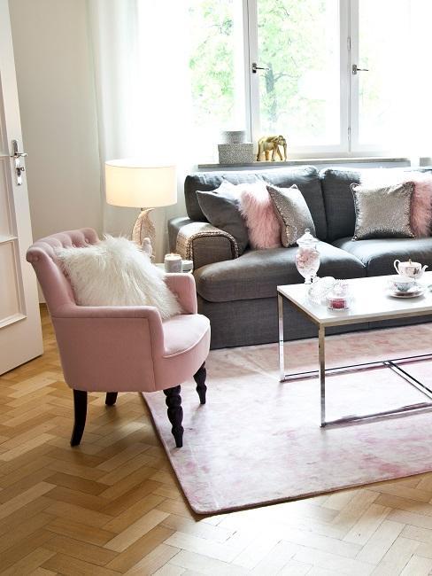 Canapé gris avec coussins roses et un fauteuil rose dans le salon.