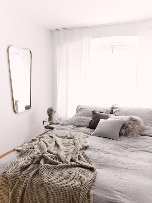 Camera da letto piccola con tessili grigi e specchio da parete