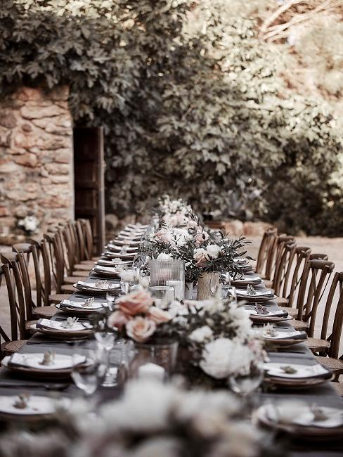 Grote, gedekte bruiloftstafel buiten met bloemen en plaatskaartjes