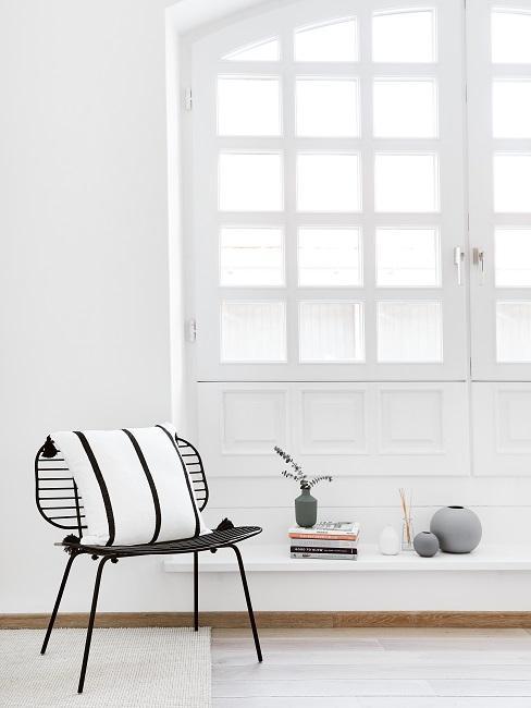 Czarne krzesło z czarno-białą poduszką dekoracyjną ustawione obok dużych drzwi tarasowych.