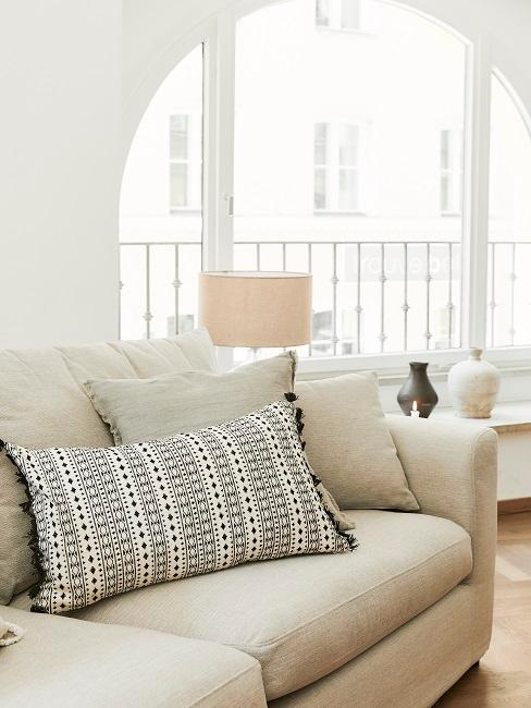 Helles Sofa mit Kissen Deko vor einem großen Fenster im hellen Raum
