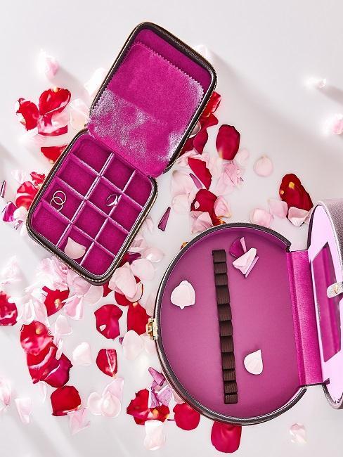 Pinke Schmuckboxen neben Rosenblättern