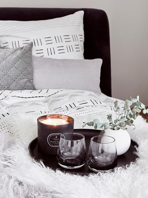 Eukalyptus in einer kleinen weißen, runden Vase auf einem schwarzen Deko-Tablett auf dem Bett im Schlafzimmer.