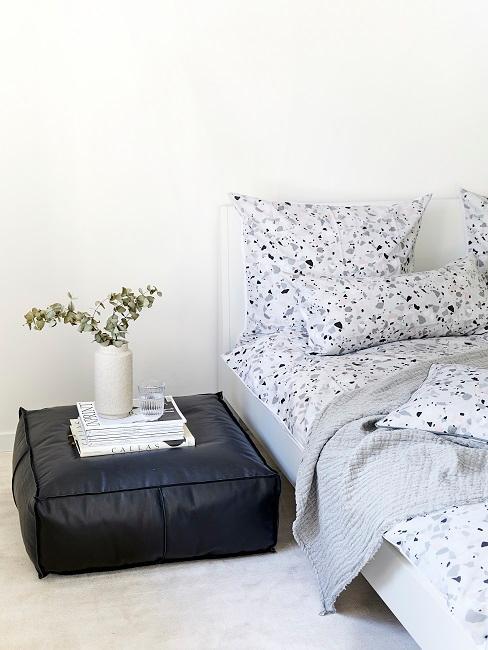 Eukalyptus in einer Vase neben dem Bett auf einem Sitzkissen aus Leder.