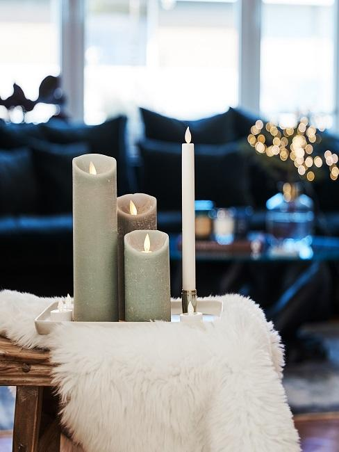 Gemütliches Wohnzimmer mit brennenden Kerzen in Grau im Wohnraum.