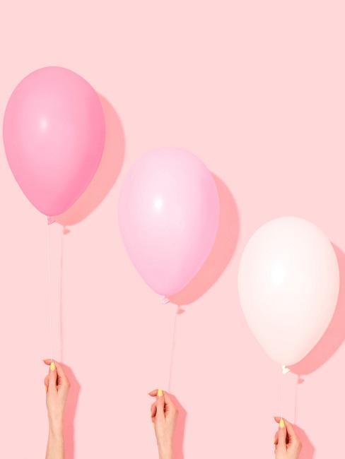 Rosafarbene Hand, davor drei rosa Luftballons, gehalten von Frauenhänden