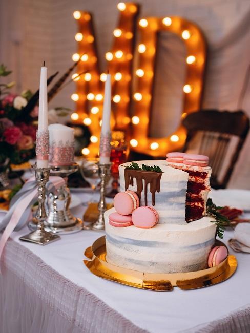 Buffet-Tisch mit Kerzen und weiterer Deko und einer großen Torte, im Hintergrund Leuchtschrift