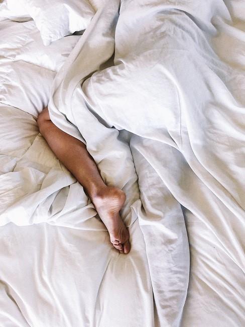 Schlafposition Seitenschläfer: Person im Bett umhüllt mit Decke, ein Fuß ist zu sehen