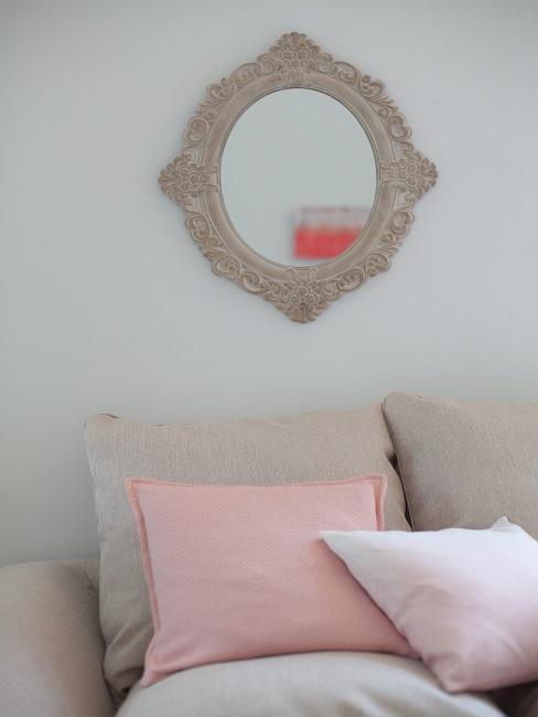 Ein beiges Sofa im Landhausstil mit ornamentalem Spiegel als Deko darüber