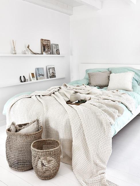 Schlafzimmer skandinavisch mit blauer Bettwäsche, Wolldecke und Korbdeko