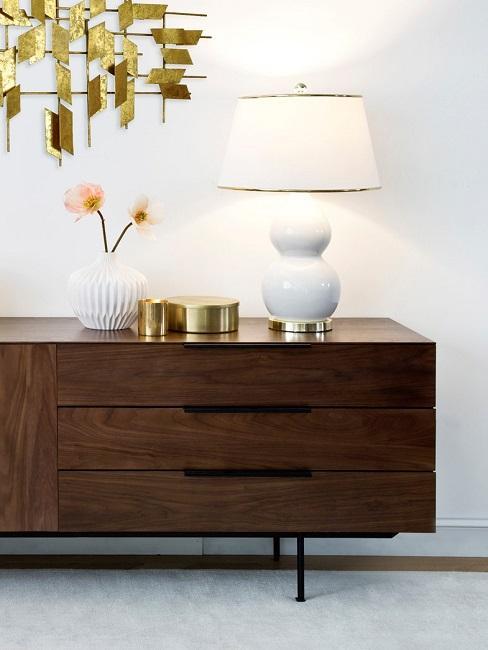 Braune Holz-Kommode mit einer weiß-goldenen Tischlampe, einer Vase und goldenen Dosen
