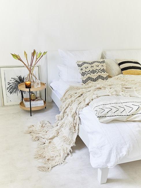 Boho Schlafzimmer in weiß und creme mit Kissen in Ethnomuster und Decke