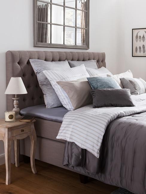 Bett in Grau mit Kissen im Landhausstil und einem Holz-Vintage-Beistelltisch sowie einem Spiegel im Fensterstil