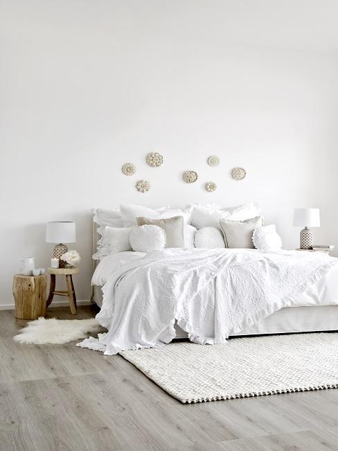 Feng Shui Schlafzimmer in weiß mit Kissen, Wanddeko, Fell und Nachttisch aus Holz